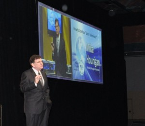 Keynote and Breakout Speaker Mike Hourigan on stage holding a keynote speech